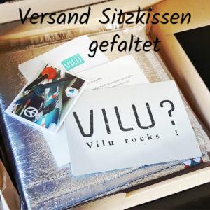 Sitzkissen von VILU, zusammengefaltet und mit Infoblatt und Visitenkarte in Klarsichthülle in noch geöffnetem Versandkarton.