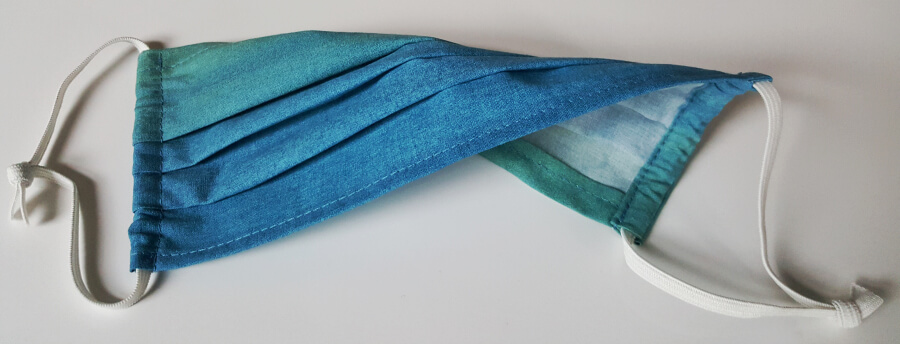 """Blaugrüne Alltags-Maske mit seitlich angebrachten Gummis, zur Befestigung """"um die Ohren"""" ."""