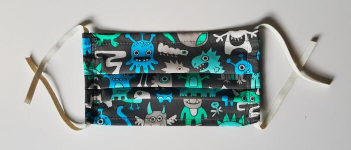 Alltagsmaske für Jungs mit blauen, grünen und grauen Monsterfiguren auf schwarzem Untergrund.