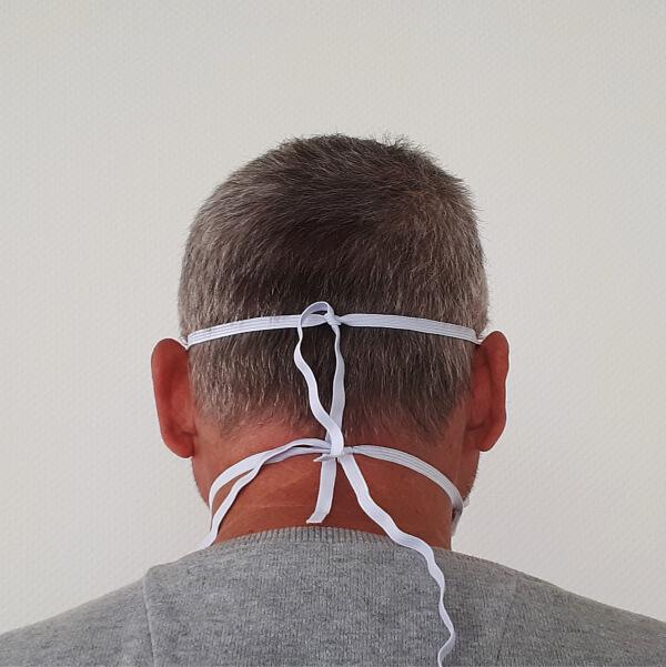 Hinterkopf-ansicht eines Mannes, der eine Alltagsmaske mit Gummibändern um den Kopf befestigt trägt.