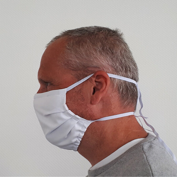 Seitenansicht eines Mannes mit weißer Communitymaske, die über Gummibänder um den Kopf fixiert wurde.