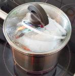 Kochtopf mit durchsichtigem Deckel auf eingeschaltetem Herd, eine weiße und eine bunte Behelfs-Schutzmaske werden gerade ausgekocht.