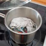 Kochtopf am Herd. Der Deckel wurde soeben vom Kochtopf abgehoben. Drinnen eine weiße und eine bunte Behelfs-Schutzmaske, die ausgekocht werden sollen.