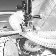 Band an FFP2-Maske wird mit einer Nähmaschine angenäht.