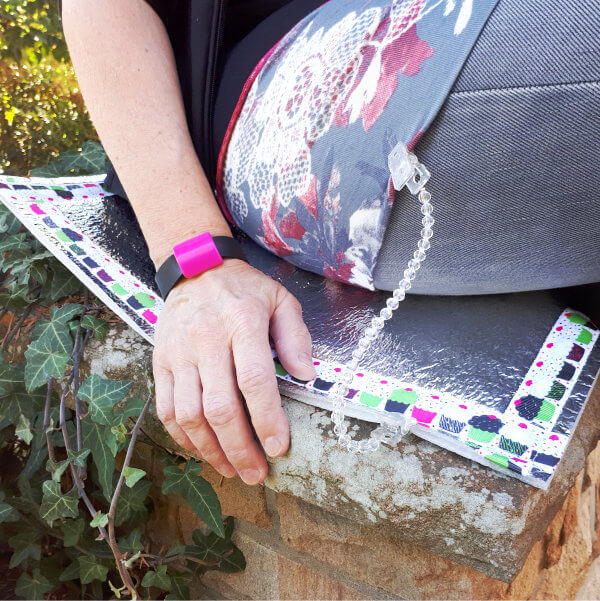 """Detailansicht einer Person, sitzend auf einem Sitzkissen, das einen efeubewachsenen, gemauerten Stein bedeckt. Das Sitzkissen ist mit einem umlaufendem """"Cupcake""""-Motiv-Ripsband umnäht und ist über das Girly-Clipbband mit der Kleidung der Person verbunden."""