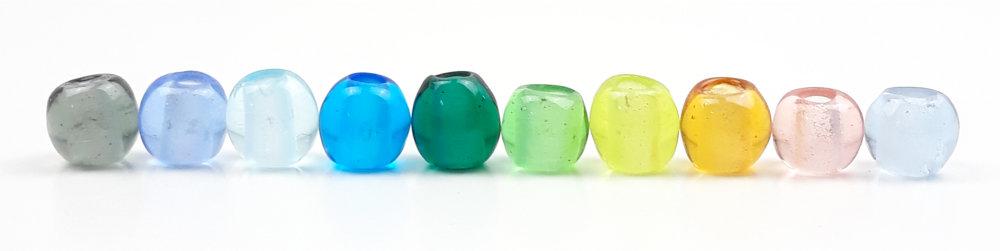 Alle 10 Farben für die Schmuckbänder mit handgedrehten Glasperlen dicht aneinander gereiht.