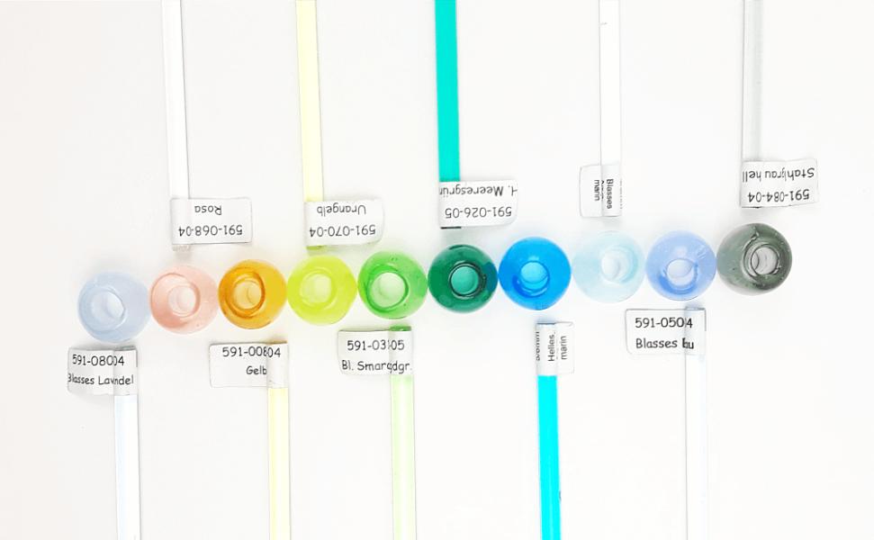 Mittig die 10 verschiedenen farbigen Großlochperlen, die im VILU-Shop erhältlich sind und jeweils dazu die farblich dazugehörigen Glasstäbe.