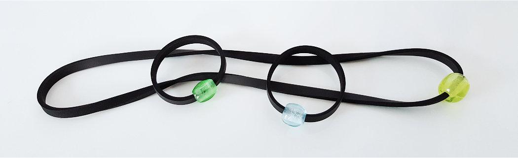 1 Neoprenhalsband mit großer, runder, gelber und 2 Neoprenarmbänder, einmal mit grüner, ovaler und einmal mit blass aquamarinfarbener, kleiner, runder Glasperle.